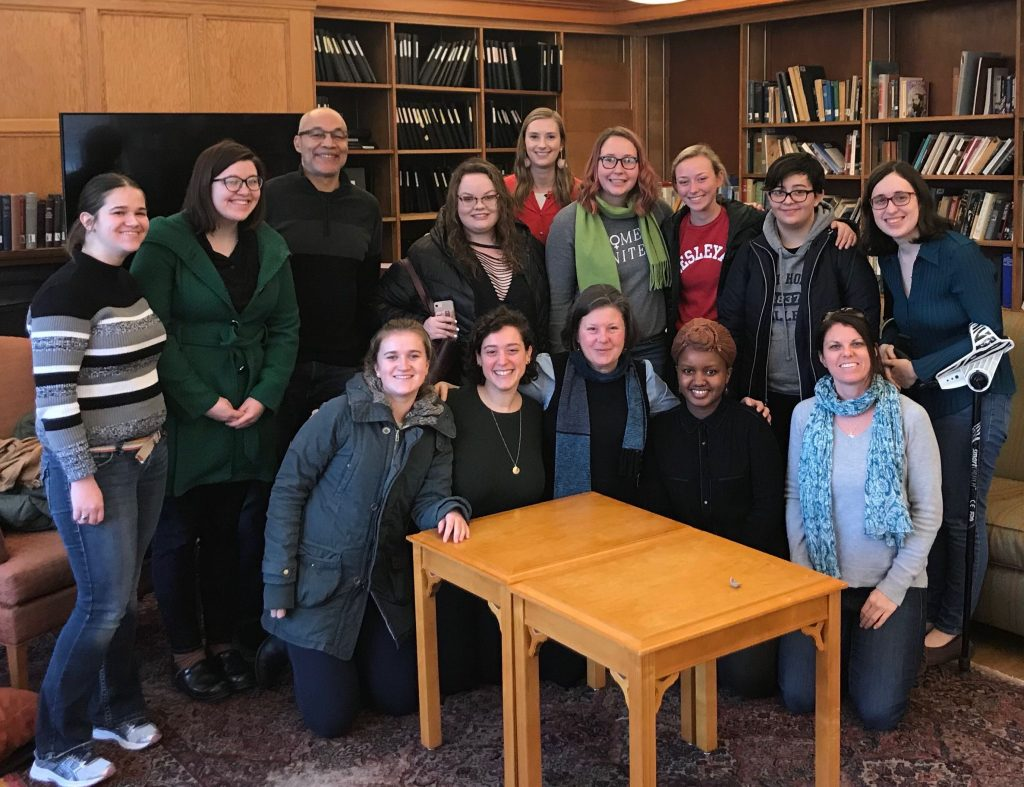 Jo crouches at the front of a group of Mount Holyoke college students