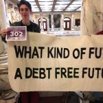 "Two young people stand in a marble-walled atrium holding a banner that reads ""What kind of future/A debt free future"""