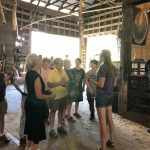 A group of people stand in a barn listening to a young woman speak.