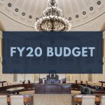 "Text reading ""FY20 Budget"" over an image of the State House interior"