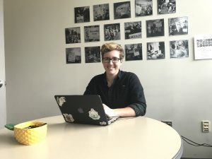 District intern, Jess, working in district office on laptop to update website.
