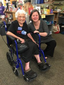 Frances Crowe smiling in a blue wheelchair with a smiling Jo Comerford crouching next to her